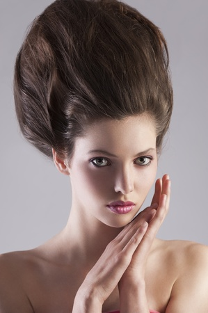 crazy hair: close up portrait of young alluring girl with dark hair and creative hairstyle posing on gray background Stock Photo