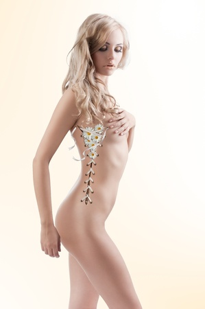 naked female body: beautiful sexy woman in a creative shot with her body open like a corset and leaves coming out
