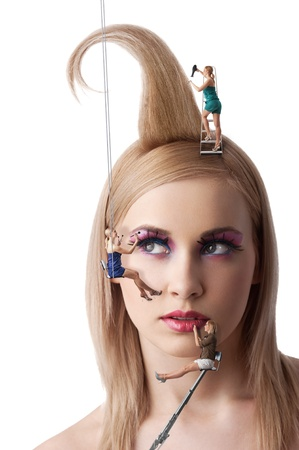 beauty portrait of blond young girl with make up and hair style under costruction with little woman working around the face photo