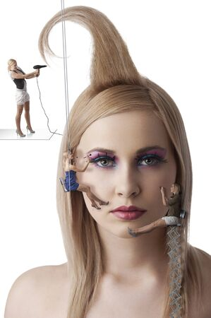 make up artist: beauty portrait of blond young woman with little make up artist working an her face Stock Photo
