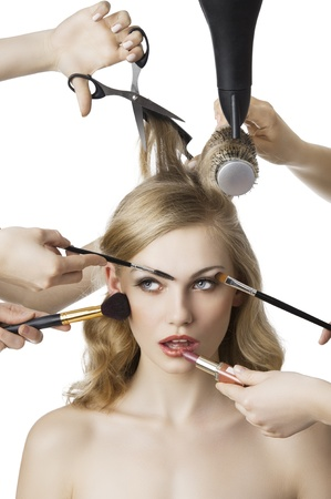 stilist: woman getting a beauty and hair style in the same time with hands making differente works, she  is in front of the camera looks up at right and her mouth is open