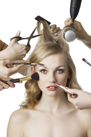 woman getting a beauty and hair style in the same time with hands making differente works, she is in front of the camera and loks in to the lens