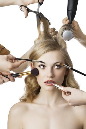 Stylist: mujer de contraer una belleza y estilo de pelo en el mismo tiempo con las manos la realización de obras differente, que se encuentra frente a la cámara y mira a la izquierda