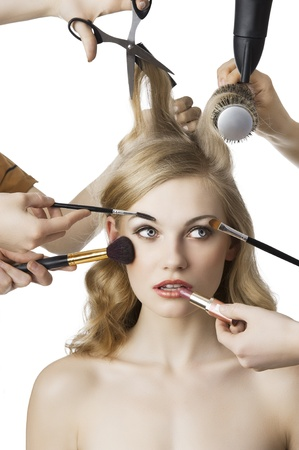 stilist: woman getting a beauty and hair style in the same time with hands making differente works, she is in front of the camera and looks at left