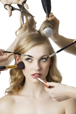 hair stylist: woman getting a beauty and hair style in the same time with hands making differente works, she is in front of the camera and looks up at right