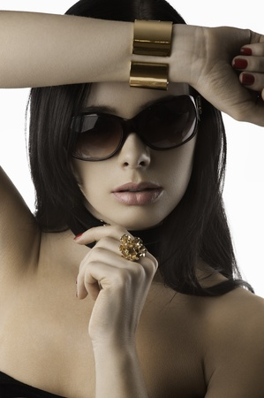 young and beautiful brunette with sunglasses red nails and fashion jewellery over white taking pose photo
