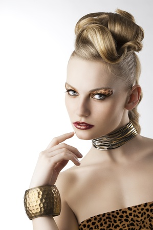 portarit: fashion beauty portarit of blond young cute girl with creative hair style and leopard make up, she is turned of three quarters looks in to the lens and has the right hand near her mouth Stock Photo