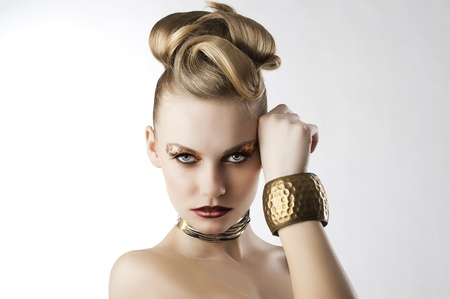 fashion beauty portarit of blond young cute girl with creative hair style and leopard make up, she is in front of the camera, looks in to the lens and has the right hand near the left part of the face Stock Photo