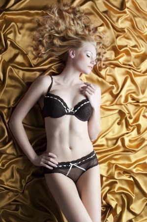 very sexy and stunning blond girl in black elegant lingerie and curly long hair sleeping on golden silk photo