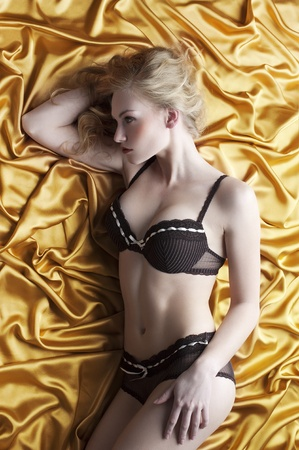 very sexy and alluring blond girl in black elegant lingerie and curly hair posing on golden silk photo
