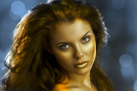 fantasy makeup: very cute young brunette with long hair with make up and shining gold color lips