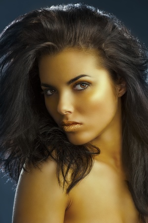 very cute girl with long dark hair,golden make up and shining gold color lips photo