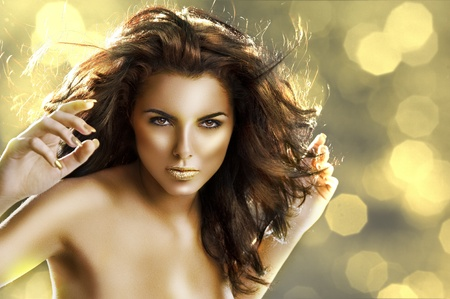fantasy makeup: very cute young brunette with long flying hair, golden make up and shining gold color lips