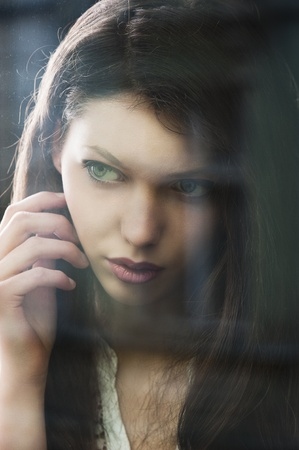 Portrait of a lovely young lady looking through glass window - Indoor in a dark cloudy day, she looks at right and has the right hand near the face photo
