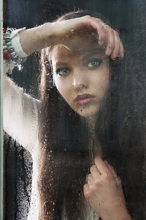 Portrait of a lovely young lady looking through glass window - Indoor in a dark cloudy day, she looks in to the lens, her head is resting on the right arm and her left hand is near the chest photo