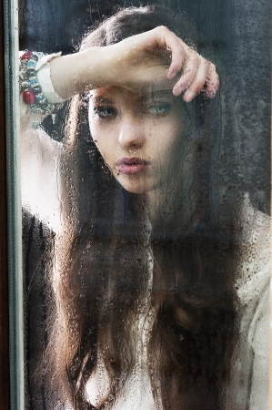 Portrait of a lovely young lady looking through glass window - Indoor in a dark cloudy day, she looks down at left,  her head is resting on the right arm and the left hand is near the chest Stock Photo