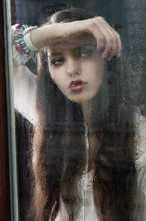 Portrait of a lovely young lady looking through glass window - Indoor in a dark cloudy day, she looks down at right and her head is resting on the right arm Stock Photo