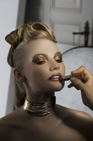 fashion portrait of cute and elegant woman doing make up on backstage with spot light on her face photo