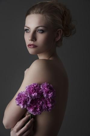 Retrato de joven mujer desnuda rubia con un poco de flor de clavel morado