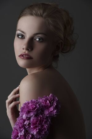 low key portrait of young blond woman with naked upper body and  purple flowers photo