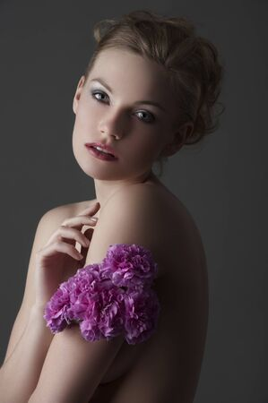 portrait of young blond elegant woman with some carnation purple flower around one arm photo