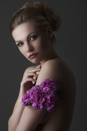 low key portrait of young blond glamor woman with some carnation purple flower around one arm photo