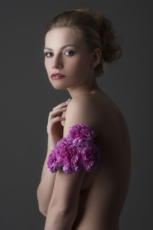 low key portrait of young blond naked woman with  flower bouquet around her arm photo