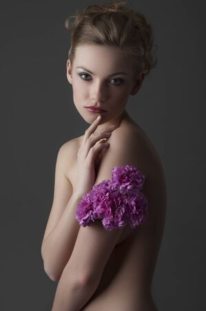 portrait of attractive young blond naked woman with some carnation purple flower around one arm photo