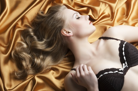 close up portrait of blond beautiful girl with well done hair style laying down on golden shining material, she is turned in profile at left and she looks down, her right hand is near the right shoulder photo