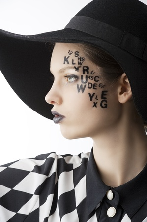 face paint: pretty and beautiful young lady with a creative make up made with letter on face and black hat and unusual shirt, she is turned on profile at right and looks in front of her