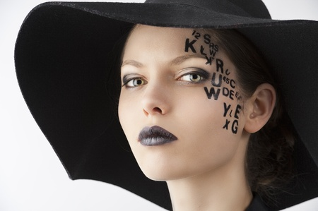 pretty and beautiful young lady with a creative make up made with letter on face and black hat and unusual shirt, she looks in to the lens with serious expression Stock Photo - 13322829