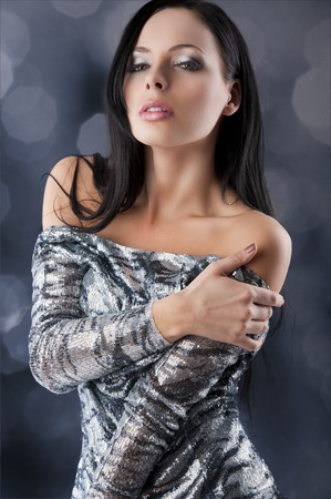 silver dress: fashion shot of sexy cheerful disco girl brunette posing on dark background in black and silver dress, she looks in to the lens with sexy eyes, her right hand is on the left shoulder