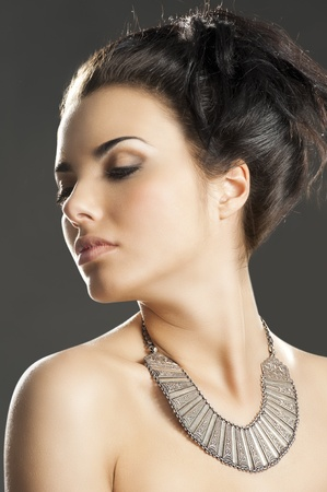 fashion beauty portrait of young pretty lady with hair style and an important old fashion silver necklace, her face is turned of three quarters at right and she looks down photo