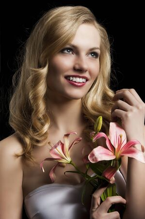 pink lips: fashion portrait of a young pretty blond girl with pink lily over black background looking in camera, she looks at left, laughs and touches her hair with right hand Stock Photo