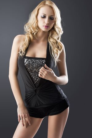 sexy black dress: elegant and sexy woman in black with shorts and with a curly hair style over black background, she is in front of the camera, looks down and touches her dress with left hand