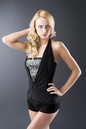 left behind: elegant and sexy woman in black with shorts and with a curly hair style over black background, she looks in to the lens, her right hand is behind the head and the left hand is on the hip
