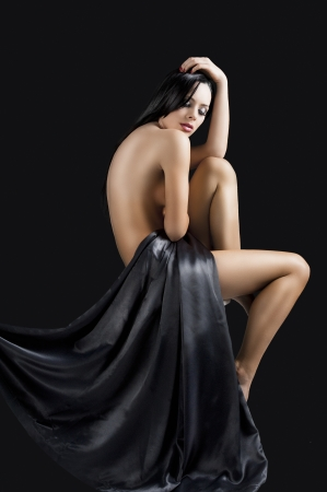 naked girl body: stunning beautiful young girl with perfect body posing naked and covering with long black material, she looks down and her left hand is on the head