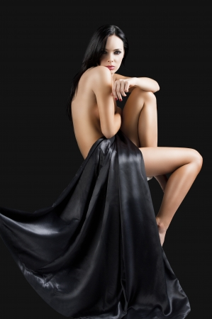 stunning beautiful young girl with perfect body posing naked and covering with long black material, she looks in to the lens, her left leg is folded and her right arm is on the left knee Stock Photo