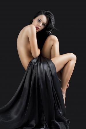 desnudo artistico: impresionante hermosa joven con un cuerpo perfecto posando desnuda y cubierta con material negro largo, la cabeza se dobla a la izquierda y que se ve en la lente