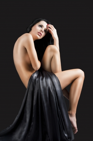 young naked girl: stunning beautiful young girl with perfect body posing naked and covering with long black material, herleft hand is near the head and she looks up with searious expression