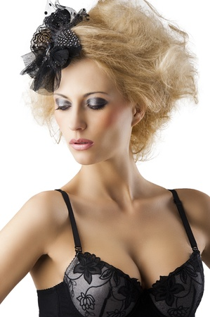 hair style with black accessory of a very beautiful blond girl wearing a black bra lingerie, she is turned of three quarters at right and looks down photo