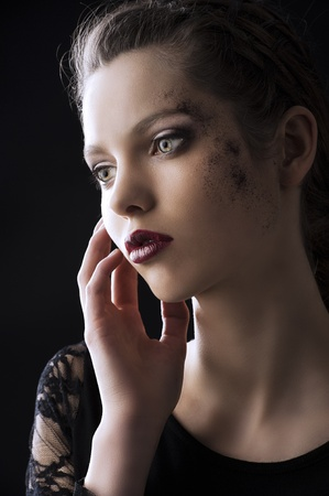 very dirty: close up portrait of very beautiful young lady actrees over a dark background with dirty make up and fashion light, she is turned of three quarters at right, she looks in front of her and her right hand is near the face Stock Photo