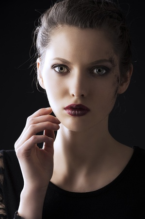 close up portrait of very beautiful young lady actrees over a dark background with dirty make up and fashion light, she is in fornt of the camera, looks in to the lens and her right hand is near the face photo