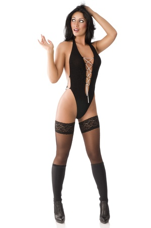 erotic: beautiful brunette in black sexy costume stockings and boots. she looks up at right with an expression of surpraise, her left hand is on the head and her right arm is folded near the shoulder.