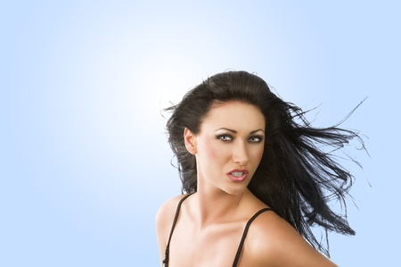 cute portrait of sensual brunette playing with hair. She looks in to the lens with attractive expression. photo