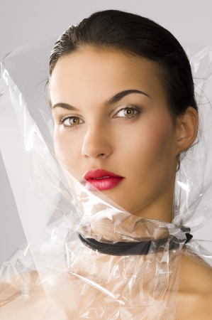 cellophane: beauty portrait of young brunette with red lips and cellophane around her face, she is slightly turned of three quarters at right and looks in to the lens Stock Photo