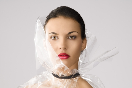 beauty portrait of young brunette with red lips and cellophane around her face, she is in front of the camera and looks in to the lens photo