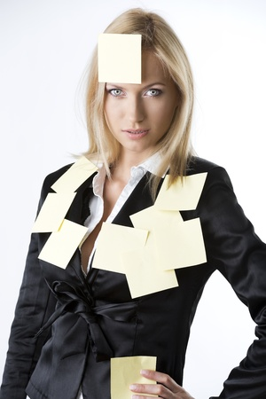 pretty business woman with black jacket and some post-it on her body, she looks in to the lens with endearing expression and her right hand is on the right hip Stock Photo - 14064081