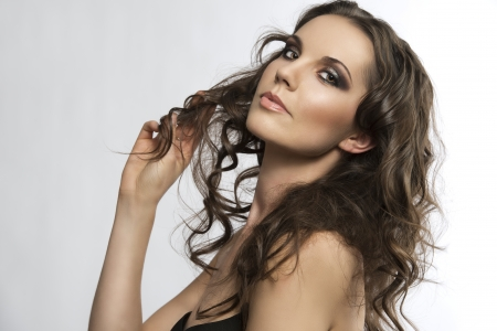bautiful girl with brown, curlyand long hair, she is turned of three quarters, looks in to the lens and takes one lock of hair with right hand photo