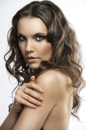 bautiful girl with brown, curlyand long hair. She is turned of three quarters, looks in to the lens and her right hand is on left shoulder photo